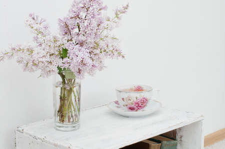 curio: Gentle spring bouquet of lilac and tea in china teacup with victorian roses on vintage shabby nightstand