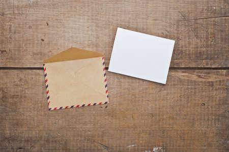Sobre de la vendimia y de la tarjeta en el fondo de madera Foto de archivo - 45356600