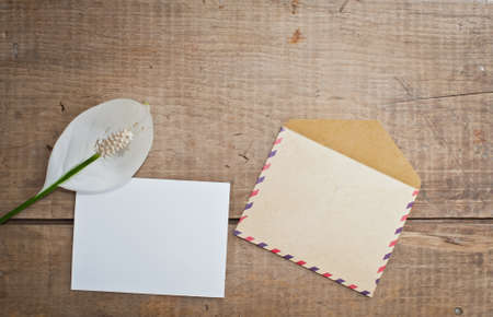 old envelope: Old envelope and card with flower on wooden background Stock Photo