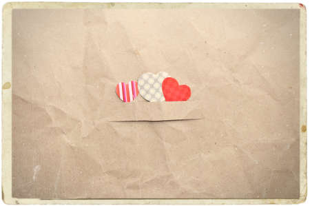 missive: three hearts on old vintage crumpled paper background