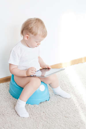 depending: little boy on potty with tablet pc on the  white carpet Stock Photo