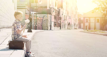 4 years old little kid sitting on pavement on old vintage suitcase and blowing dandelion seeds in sunny summer morning on deserted street