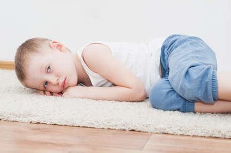 grieved: Sad 4 years old boy laying on carpet