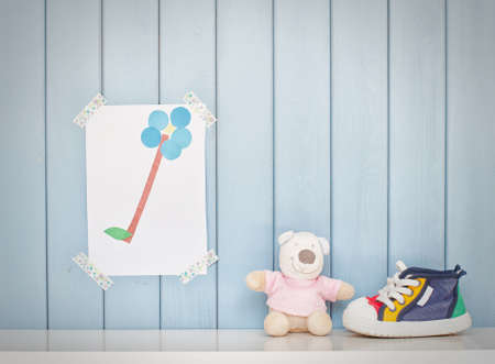 Funny colorful child picture on the wall in the room, tiny baby shoes and teddy bear toy Stock Photo