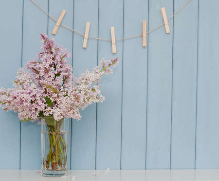 empty wooden clothespins on the rope and bunch of lilac