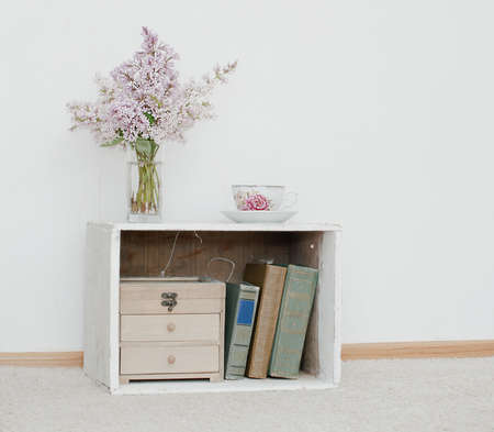 curio: gentle bunch of lilac and china teacup on vintage shabby bedside table with wooden box and ancient books inside