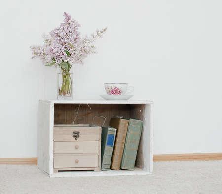 Montón suave de color lila y taza de té de porcelana en la mesita de noche lamentable de la vendimia con la caja de madera y libros antiguos en el interior Foto de archivo - 45355879