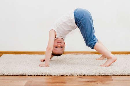 Niño feliz está jugando en la alfombra blanca en su habitación Foto de archivo - 45355890