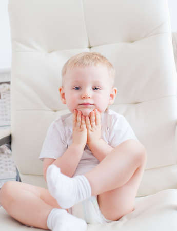 keen: Cute little boy is sitting on the white chair in baby room Stock Photo