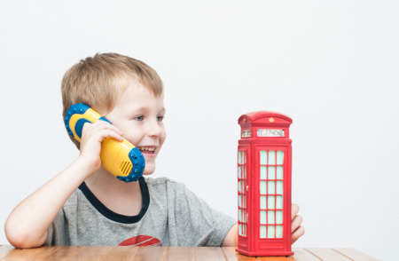 cell phone booth: Little cheerful boy talking on the phone and vintage british red telephone booth Stock Photo