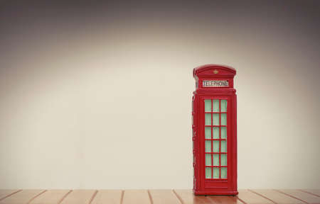 telephonic: vintage red british phone booth souvenir on white background