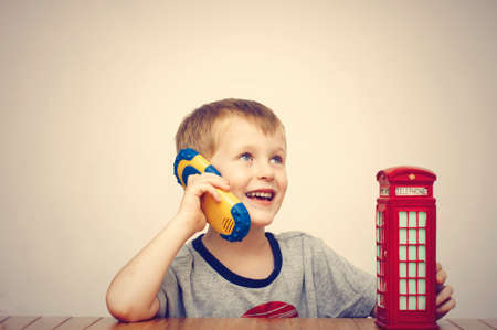 telephonic: Boy talking on the phone and vintage british red telephone booth