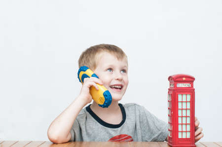 cell phone booth: Boy talking on the phone and vintage british red telephone booth