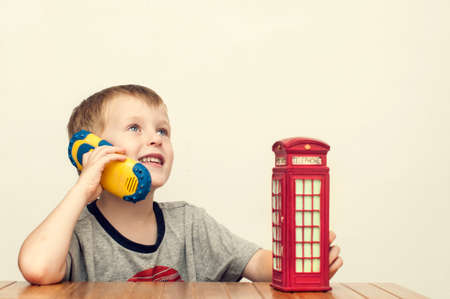 Little cheerful boy talking on the phone and vintage british red telephone booth Stock Photo