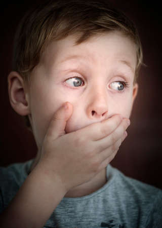 Scared little boy , listening scary story and closing his mouth by his hand