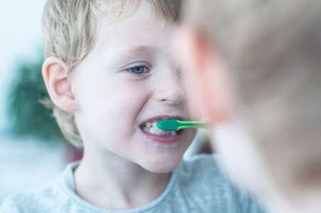 El pequeño muchacho lindo cepillarse los dientes y mirando el espejo en el baño; Foto de archivo - 57717150