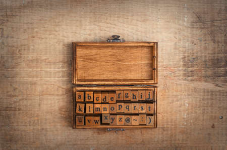 puzzle background: wooden stamps alphabet in old vintage box on  grunge background