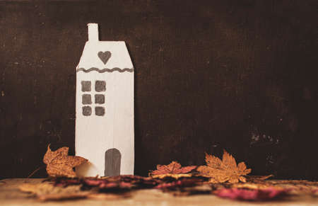 life at home: vintage cardboard decorative house and autumnal dry maple leaves