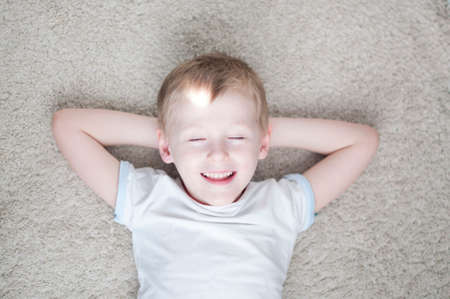 impish: happy little kid is dreaming on a carpet