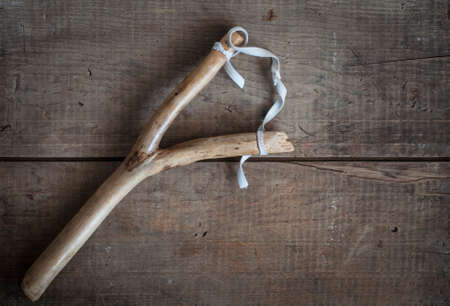 misbehave: old vintage slingshot toy on wooden background