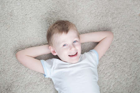 impish: smiling little kid at home on the beige carpet