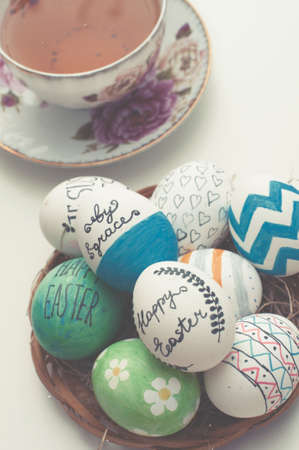 hallelujah: Easter  decorated eggs in a straw plate and english tea on white background