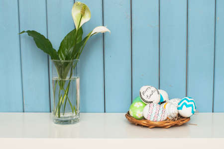 hallelujah: easter eggs and flowers in a glass on the blue wooden background