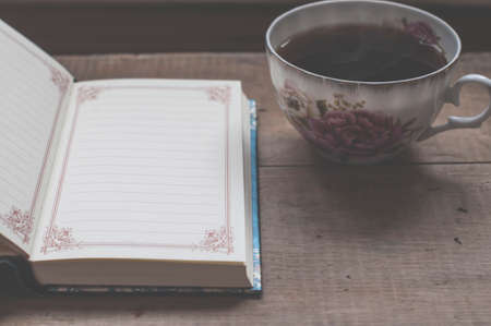 still life with coffee mug and blank notebook on vintage wooden table