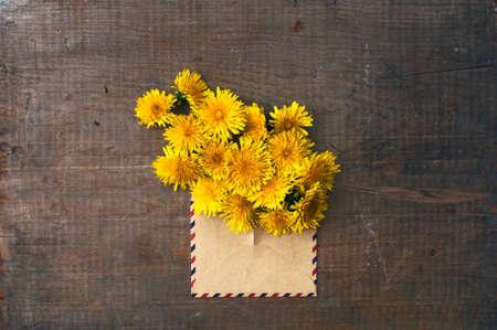 old envelope: dandelion flowers in the vintage envelope on the old wooden background