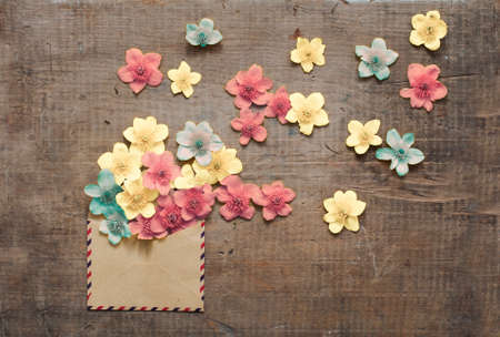 old envelope: beautiful flowers in the old envelope on wooden table Stock Photo
