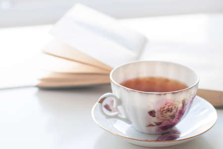 soul food: Black english tea in porcelain cup decorated with victorian rose and ancient book and on the vintage white table Stock Photo