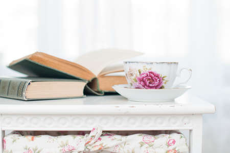 Breakfast in the morning with books and tea in china teacup in cozy bedroom on white nightstand