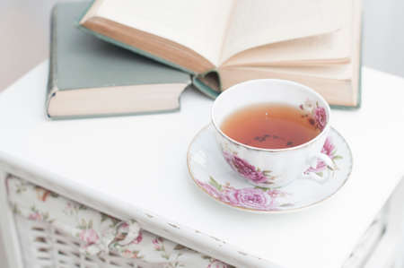 soul food: Breakfast in the morning with books and tea in china teacup in cozy bedroom on white nightstand