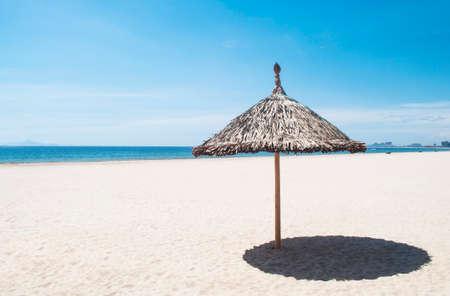 straw umbrella on a tropical beach on blue sky background Stock Photo