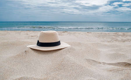 downshift: straw hat in sand beach and blue sea and sky on the background