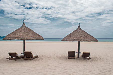 downshift: Straw parasols with chaise lounges in the beach with white sand Stock Photo