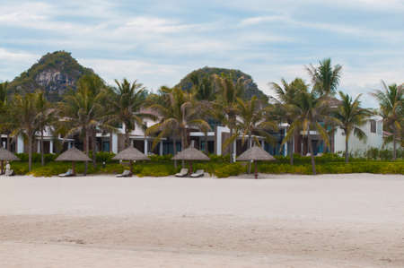 My Khe beach with white sand, straw parasols and palms in Danang, Vietnam