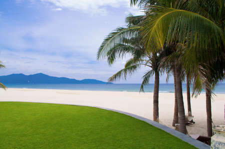 downshift: Beautiful seascape with blue sea, white sand and green palms in the My Khe beach, Vietnam Stock Photo
