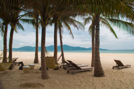 Sunbeds, with sand, blue sea and palms in the My Khe beach, Danang, Vietnam