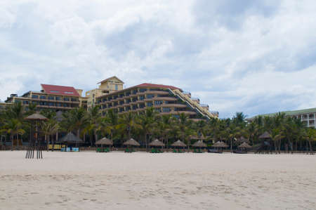 downshift: Hotel, palms, straw umbrellas and white sand in the My Khe beach, Danang, Vietnam
