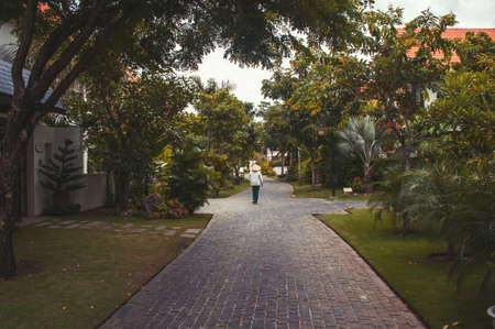 verandah: cozy street, surrounded by greenery and lonely man in Vietnamese hat