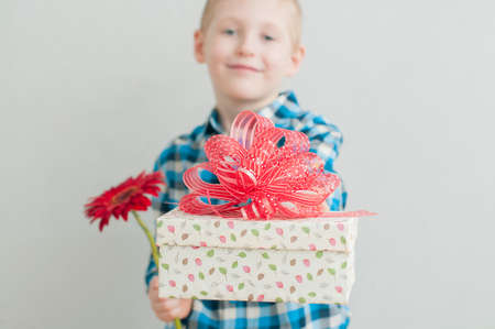 Cheerful little boy with red flower and gift box