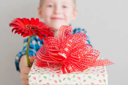 valentines day mother s: Cheerful little boy with red flower and gift box