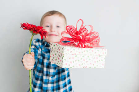 赤い花とギフト ボックスを持った幸せな陽気な少年 写真素材
