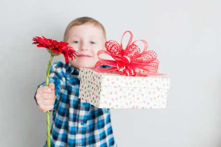 Gelukkige vrolijke jongetje met rode bloem en gift box