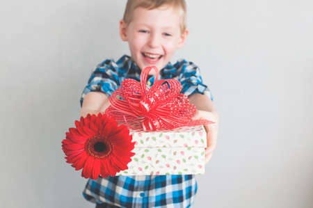 Happy cheerful little boy with red flower and gift box in a banner