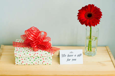 a gift box with red ribbon, greeting card and a flower Stock Photo