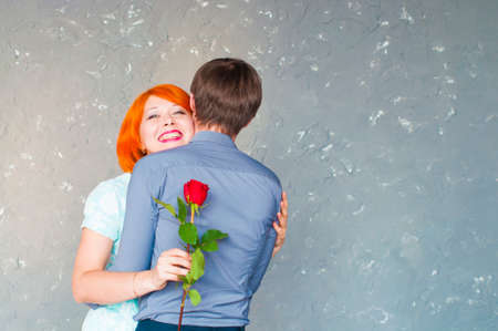 man and smiling woman with red rose are cuddling each other and happy