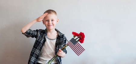 Proud cheerful boy celebrating Memorial day with flowers and American flag Stock Photo