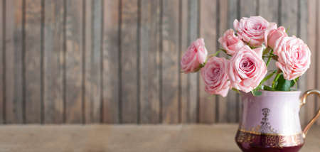 Beautiful pink roses in a vintage jug on rustic wooden background Stock Photo
